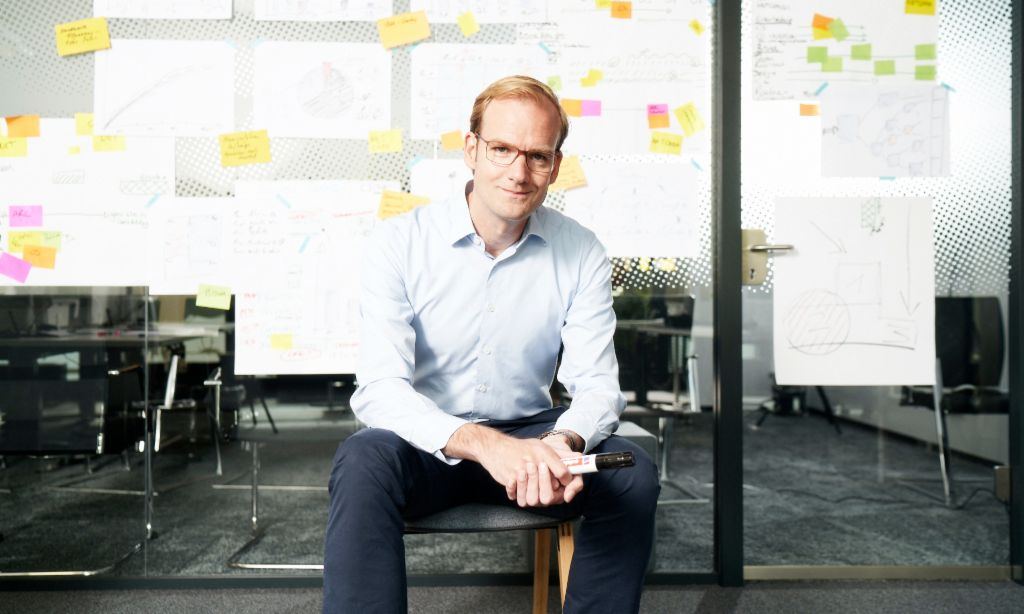 Receivables purchasing: Matthias Schmidt, Head of Operational Debt Purchase at EOS Group, sits in front of a wall covered in post-its and other notes.