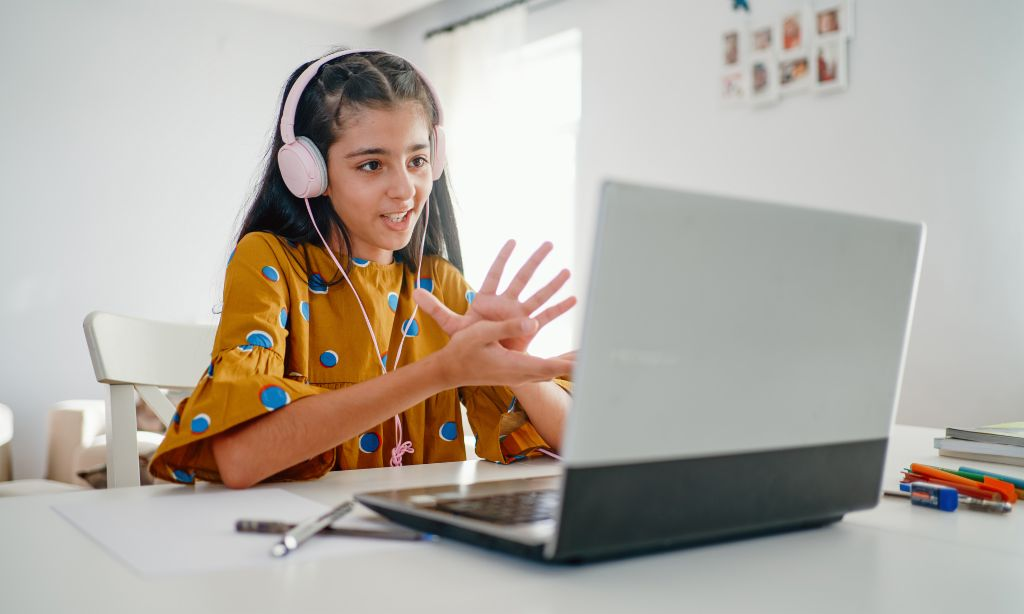 Financial literacy means responsibility: A girl sits at a laptop and takes part in online learning.