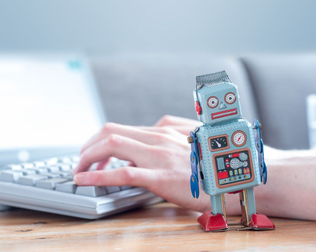 Robotic process automation: A robot figure in front of a computer.