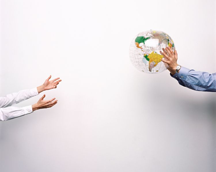 Two men throw a plastic globe to one another